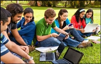Students sitting on a grass field (photo)
